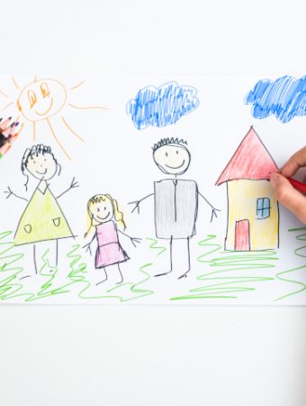 child's hand sketches a picture of family - fine motor activities