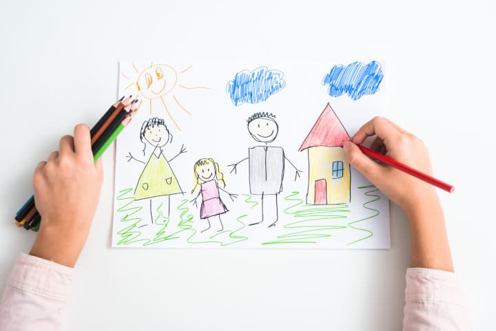 child's hand sketches a picture of family. drawing is a fine motor activities.
