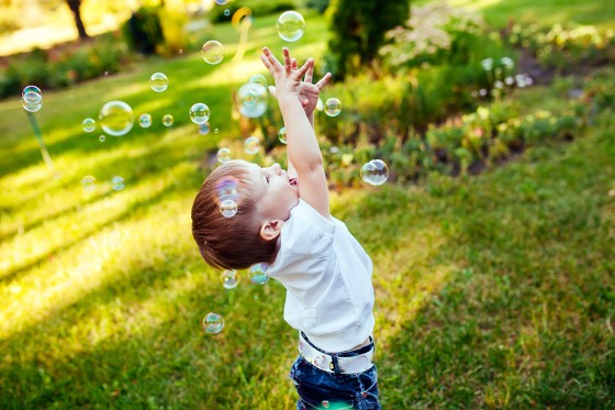 A child tries to catch soap bubbles in the air. Kids will love this Bubble Blowing Poking Experiment.
