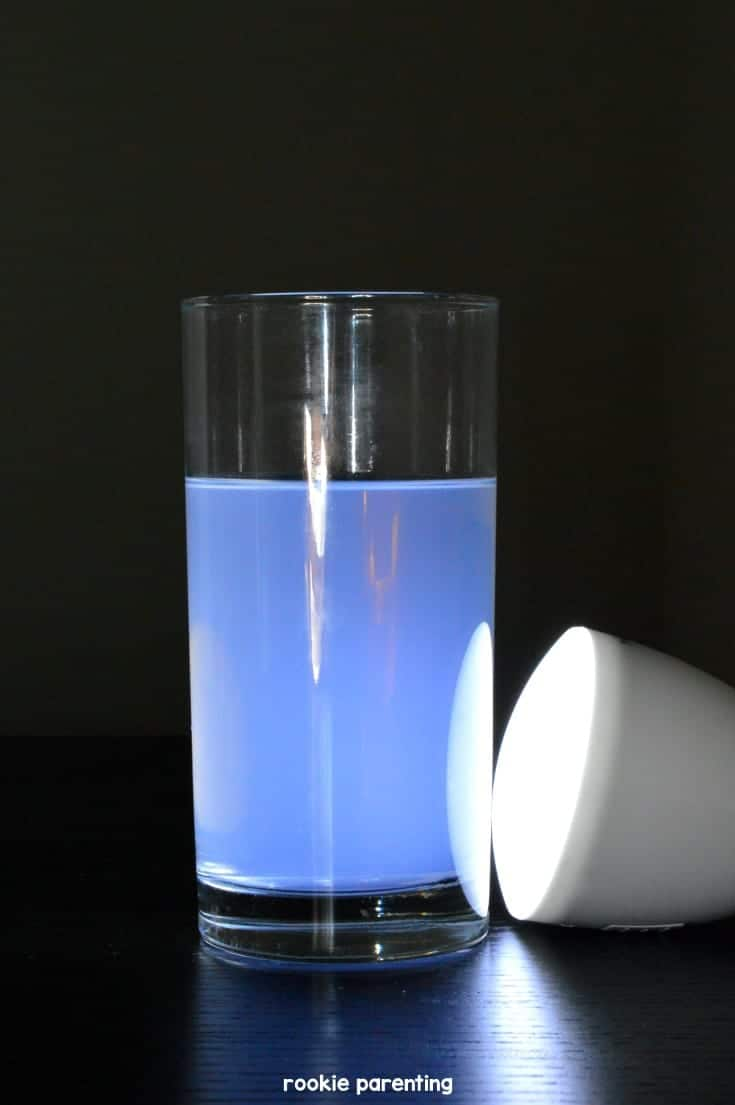 Glass with blue water, light shining on it