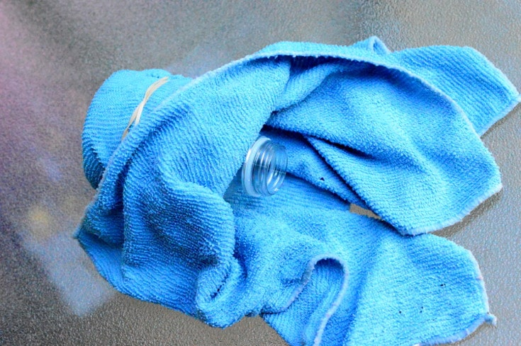 bottle neck can be seen from underneath the towel