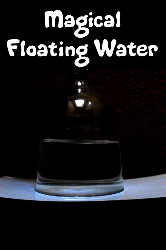 An upside down wine glass containing water is holding a piece of paper, as if the water is floating in the air.