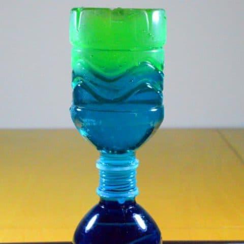 bottle of green-blue water is placed upside down on top of a bottle of dark blue water