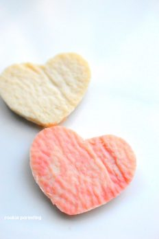 2 heart shaped plastic made with milk and vinegar, one ivory and one pink in color