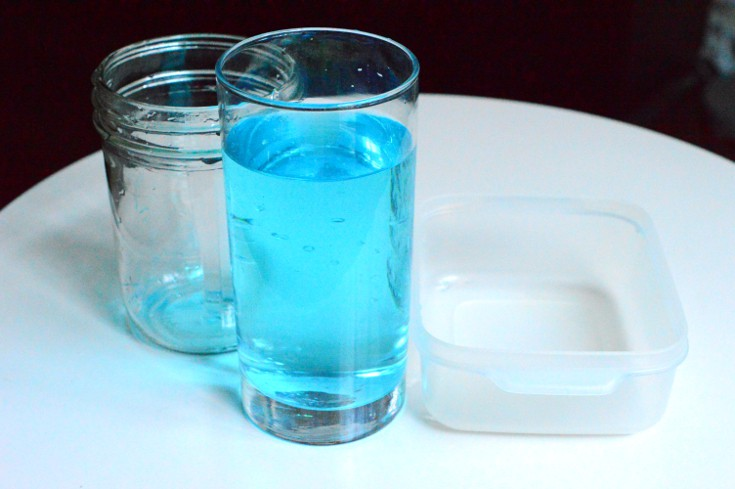 3 containers with different sizes and shapes, one of them contains blue water.